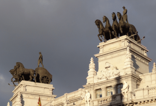 Detalles en la calle de Alcalá. Las cuadrigas de la antigua sede bancaria de BBVA vigilan el cruce con la calle Sevilla
