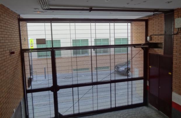 Una puerta de garaje de un pequeño edificio de vivienda colectiva en España